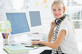 Casual woman with headset at computer desk in office