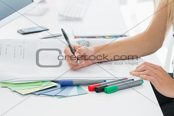 Artist drawing something on paper with pen at office