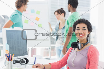 Casual woman with group of colleagues behind in office