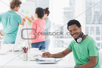 Casual man with group of colleagues behind in office