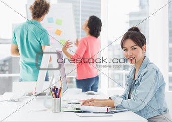 Casual woman using computer with colleagues behind in office