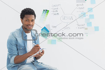 Smiling male artist writing notes in front of whiteboard