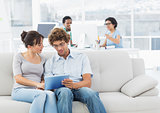 Casual couple using digital tablet with colleagues at creative office