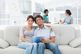 Couple using digital tablet with colleagues at creative office