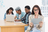 Woman using digital tablet with colleagues behind in office