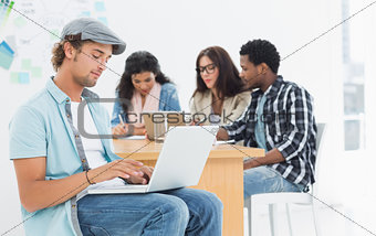 Casual man using laptop with colleagues behind in office