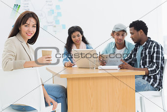 Casual woman holding take away coffee cup with colleagues behind in office