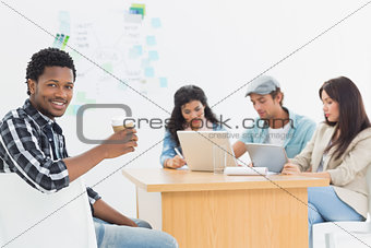 Man holding take away coffee cup with colleagues behind