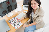 Female artist sitting at desk with computers in office