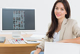 Female artist sitting at desk with computer in office