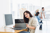Casual woman working at desk with colleagues behind in office