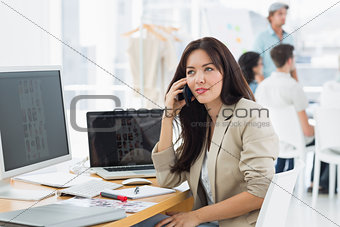 Woman on call at desk with colleagues behind in office