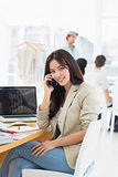 Casual woman on call at desk with colleagues behind in office