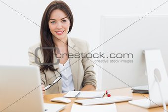 Young woman with computers at desk in office