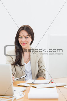Well dressed woman with laptop at desk in office