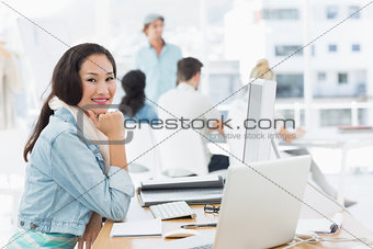 Casual young woman with colleagues behind in office