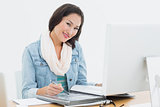 Smiling casual woman with catalog in front of computer in office
