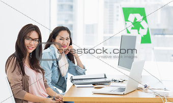 Female artists at desk with recycling sign in background at office