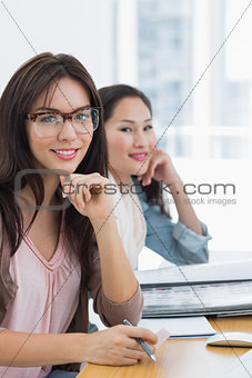 Portrait of two casual female artists working at desk