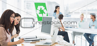 Artists working at desks with recycling sign in background at office