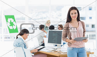 Female artist holding digital tablet with colleagues in background at office