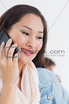 Beautiful casual young woman using mobile phone in office