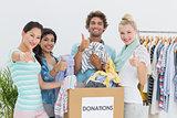 People with clothes donation gesturing thumbs up