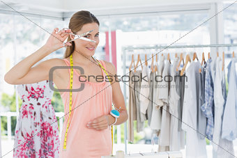 Beautiful female fashion designer holding scissors in store