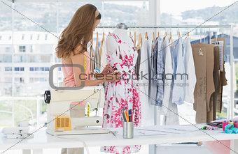 Female fashion designer working on floral dress
