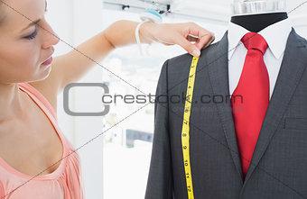 Female fashion designer measuring suit on dummy