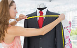 Female fashion designer measuring suit on dummy