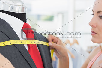 Closeup of a female fashion designer measuring suit on dummy