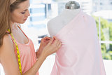 Beautiful female fashion designer working on pink fabric