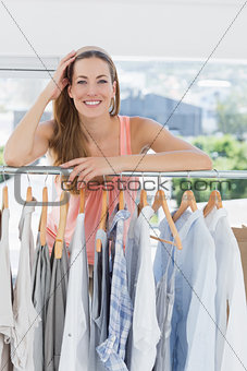 Beautiful female fashion designer with rack of clothes in store