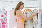 Beautiful fashion designer looking at clothes on rack