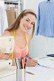 Smiling fashion designer working on her designs