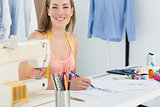 Smiling female fashion designer working on her designs