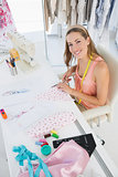 Young female fashion designer working on fabrics