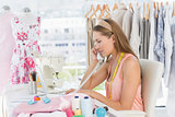 Young female fashion designer using phone