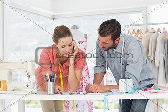 Fashion designers at work in bright studio