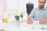 Fashion designer working on his designs in studio