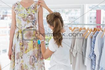 Female fashion designer measuring model