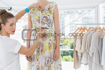Female fashion designer measuring model