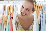 Happy female customer amid clothes rack