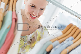 Beautiful female customer selecting clothes at store