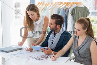 Three fashion designers discussing designs