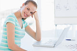 Smiling young casual woman in front of laptop at office