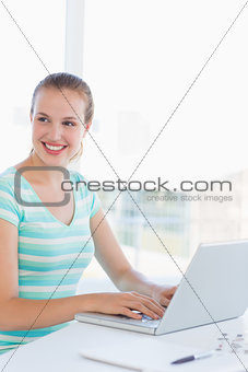 Young casual woman using laptop at a bright office