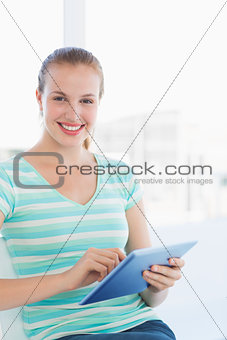 Beautiful young casual woman using digital tablet