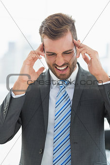 Closeup of a young businessman with headache